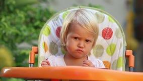 Lilla flickan sitter i stol och äter frukt lager videofilmer