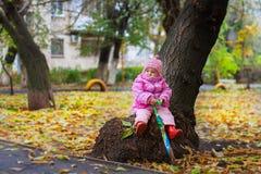 Lilla flickan sitter med ett paraply på en stump nära ett träd i nedgången Fotografering för Bildbyråer