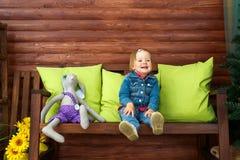 Lilla flickan sitter och ler arkivfoton