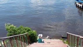 Lilla flickan sitter på en träpir som tycker om havssikt på en solig dag arkivfilmer