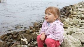 Lilla flickan sitter på flodbanken lager videofilmer