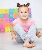 Lilla flickan sitter på golv i förträning royaltyfria foton