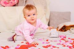 Lilla flickan sitter på mjöl bland pappers- hjortar som spelar med leksakbilen Arkivfoto