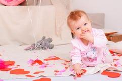 Lilla flickan sitter på mjöl bland pappers- hjortar som stänger munnen Royaltyfria Bilder
