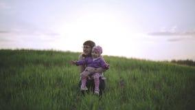 Lilla flickan sitter på varven av mamman utomhus lager videofilmer