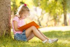 Lilla flickan sitter under ett stort träd på parkera och läser en bok arkivbilder