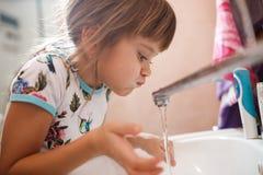 Lilla flickan sköljer hennes mun med vatten, når han har borstat dina tänder i badrummet royaltyfri foto
