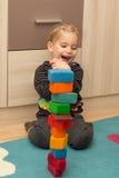 Lilla flickan ska vara glad om ett torn av tegelstenar Royaltyfri Foto
