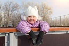 Lilla flickan skrattar och åker skridskor på isen arkivbild