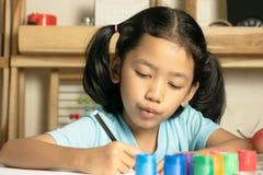 Lilla flickan skriver en bok royaltyfri foto
