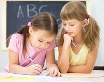 Lilla flickan skriver genom att använda en penna royaltyfria bilder