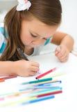 Lilla flickan skriver genom att använda en penna royaltyfri fotografi