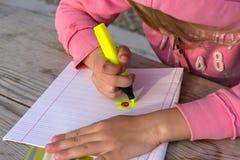 Lilla flickan skriver i en anteckningsbok på naturen royaltyfri bild