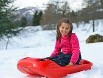 Lilla flickan som över ler, guppar på det snöig berget Arkivbilder