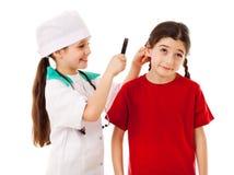 Lilla flickan som doktor kontrollerar öronen arkivfoto