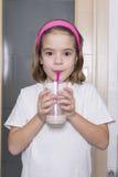 Lilla flickan som dricker ett exponeringsglas av, mjölkar arkivbilder