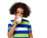Lilla flickan som dricker ett exponeringsglas av, mjölkar Fotografering för Bildbyråer