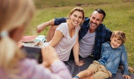 Lilla flickan som fotograferar familjen under picknick på, parkerar arkivbilder