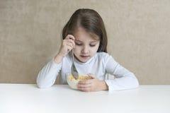 Lilla flickan som har frukostmysli med, mjölkar Royaltyfri Fotografi