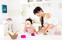 Lilla flickan som hjälper hennes moder, förbereder mat i köket Arkivfoto