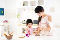 Lilla flickan som hjälper hennes moder, förbereder mat i köket Arkivbild