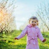 Lilla flickan som kör i solig dag för vår Bearbeta för konst Arkivfoto