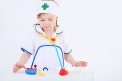 Lilla flickan som kläs som sjuksköterska, spelar med medicinska instrument för leksaken Arkivfoto