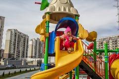 Lilla flickan som kläs varmt, i lekar för en hatt och omslagspå lekplatsen med glidbanor och gungor i borggården av residentiaen arkivfoton