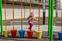 Lilla flickan som kläs varmt, i lekar för en hatt och omslagspå lekplatsen med glidbanor och gungor i borggården av residentiaen arkivfoto