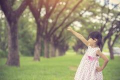 Lilla flickan som låtsar för att vara en superhero parkerar in royaltyfri foto