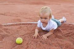 Lilla flickan som ligger på tennisbanan bollkalle little tennis Fotografering för Bildbyråer