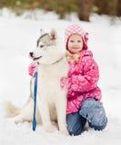 Lilla flickan som omfamnar den hasky hunden i vinter, parkerar arkivbild