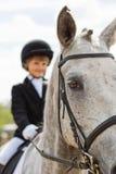 Lilla flickan som rider en häst, deltar i konkurrenser Sommarbygd Royaltyfria Bilder