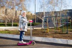 Lilla flickan som rider en sparkcykel i, parkerar p? en solig v?rdag Aktiv fritid och utomhus- sport f?r barn royaltyfria bilder