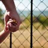 Lilla flickan som rymmer hennes farsa för handen för fader` s, rymmer hans hand för dotter` s på en gå runt om zoo fyrkant royaltyfri fotografi