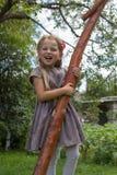Lilla flickan som skrattar krama ett träd, den härliga blonda flickan, omfamnar ett träd och le Royaltyfri Foto