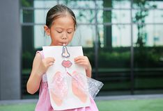 Lilla flickan som spelar att blåsa med, simulerar att andas av lungorna vart begreppshanden har den sena pillen f?r sjukv?rdhj?lp royaltyfri foto