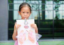 Lilla flickan som spelar att bl?sa med, simulerar att andas av lungorna vart begreppshanden har den sena pillen f?r sjukv?rdhj?lp royaltyfria foton