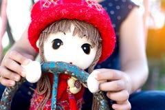Lilla flickan som spelar med henne, behandla som ett barn - dockan Arkivbilder