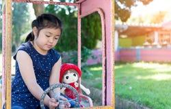 Lilla flickan som spelar med henne, behandla som ett barn - dockan Royaltyfri Bild