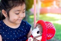 Lilla flickan som spelar med henne, behandla som ett barn - dockan Arkivfoton