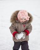 Lilla flickan som spelar med, kastar snöboll Royaltyfri Foto