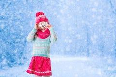 Lilla flickan som spelar med leksaksnö, flagar i vinter parkerar arkivfoto