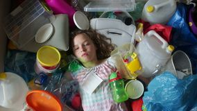 Lilla flickan som st?nger hennes ?gon omger in, av plast- avfall, plastp?sar och avskr?de Milj?f?roreningbegrepp lager videofilmer