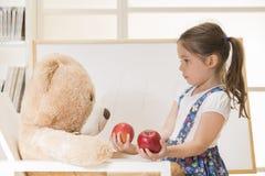 Lilla flickan som undervisar hennes leksakbjörnvän att räkna med äpplen, sköt inomhus Royaltyfria Bilder