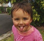 Lilla flickan som visar hennes tunga och hennes tecken, foto tog i Nya Zeeland, foto är användbar på vykortet, kalendern, garde Arkivbild