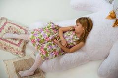 Lilla flickan sover på en vit stor nallebjörn arkivfoto