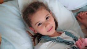 Lilla flickan sover s?tt i s?ng, vaknar upp och ser kameran, ultrarapid arkivfilmer