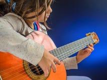 Lilla flickan spelar den klassiska gitarren Arkivbild