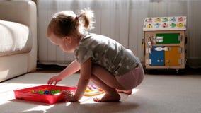 Lilla flickan spelar en lek av framkallning av motorisk expertis, mot efterkrav en m?rkes- flerf?rgad mosaik f?r barn, utveckling arkivfilmer